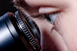 Close up of forensic scientist looking down the eyepieces of a microsocpe