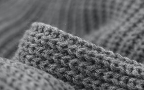 Close up of grey knitted fabric made from wool fibres